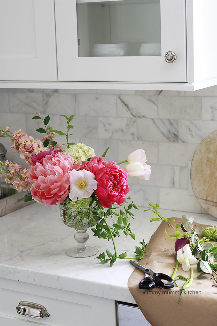 DIY floral centerpiece with pink peonies, tulips, and greenery in a white kitchen.