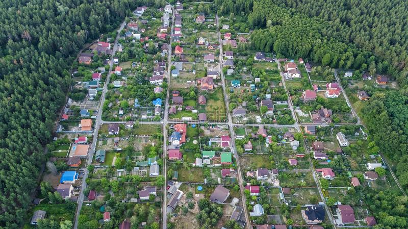 Aerial top view of residential area summer houses in forest from above, countryside real estate and small dacha village in Ukraine. Kyiv stock photography