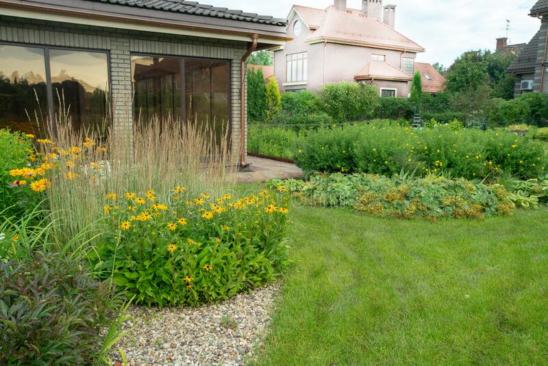 Amazing garden with perennials and grass meadow near dacha  in `Belgian village`. A magnificent garden with perennials and a country house neighboring in a royalty free stock image