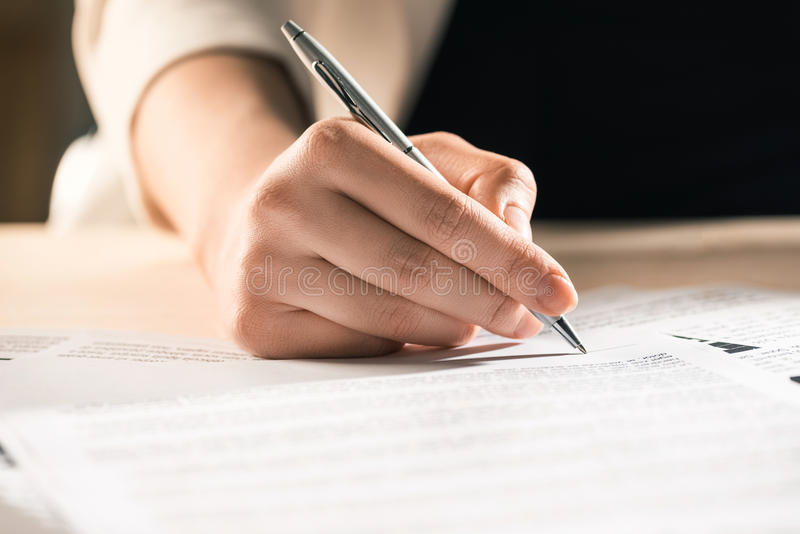 Businesswoman signing contract documents sitting at table royalty free stock images