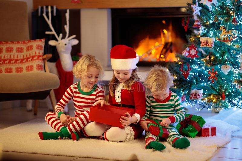 Child at Christmas tree. Kids at fireplace on Xmas. Children at Christmas tree and fireplace on Xmas eve. Family with kids celebrating Christmas at home. Boy and royalty free stock photography