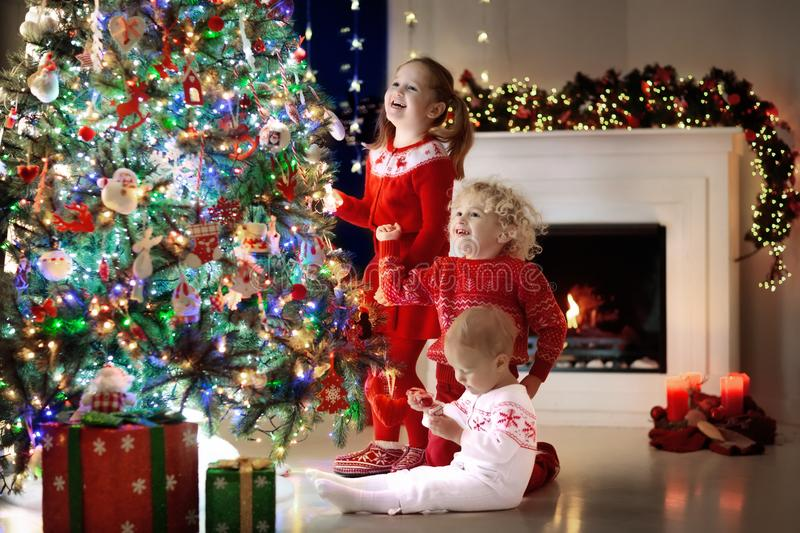 Children at Christmas tree. Kids at fireplace on Xmas eve. Children at Christmas tree and fireplace on Xmas eve. Family with kids celebrating Christmas at home stock photography