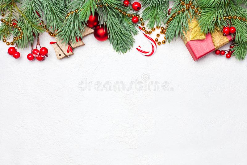 Christmas border composition with green Xmas fir branch, red holly berries and baubles on white texture stucco plaster background royalty free stock photos