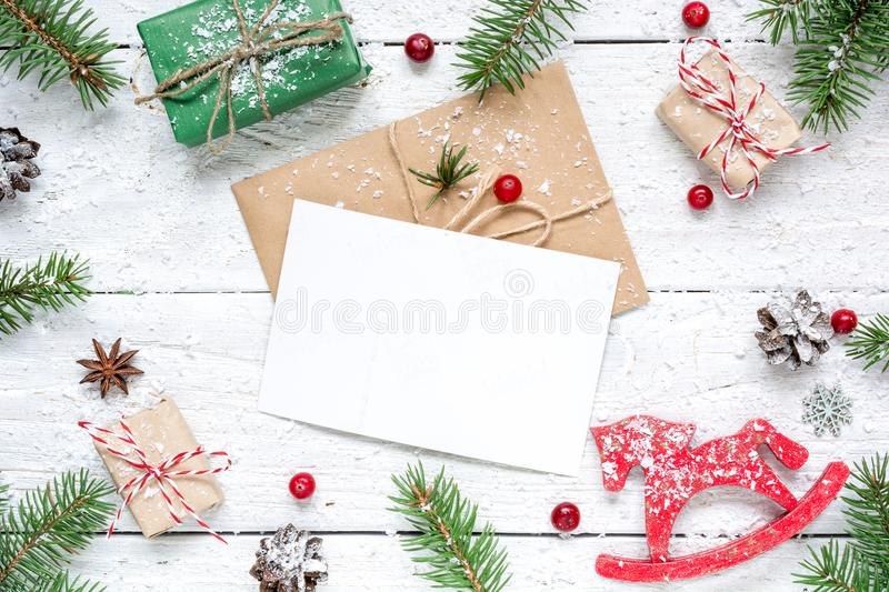 Christmas composition with blank greeting card. fir tree branches, horse toy, gift boxes and cones frame stock images