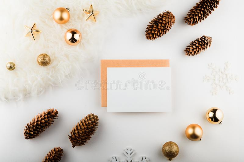 Christmas composition. Paper blank, golden decorations on white background. Flat lay, top view, copy space, square. stock photo