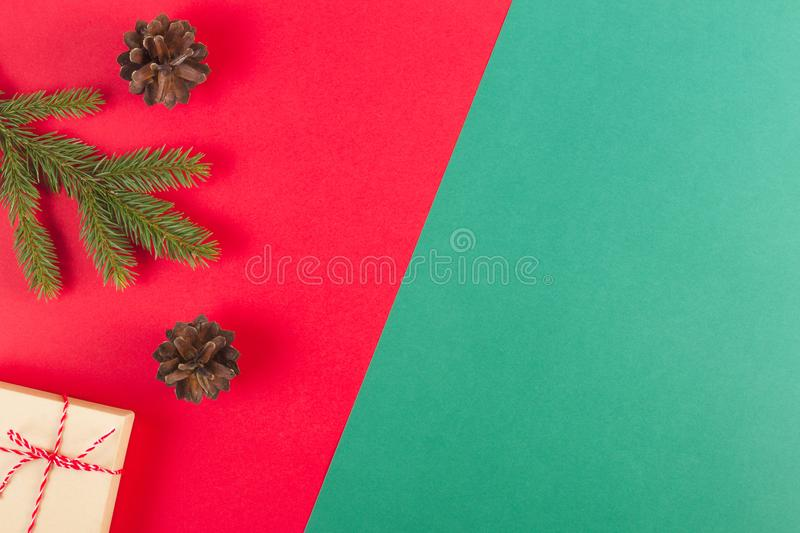 Christmas composition on red and green background. Green fir tree branch, pine cones and present box royalty free stock photos