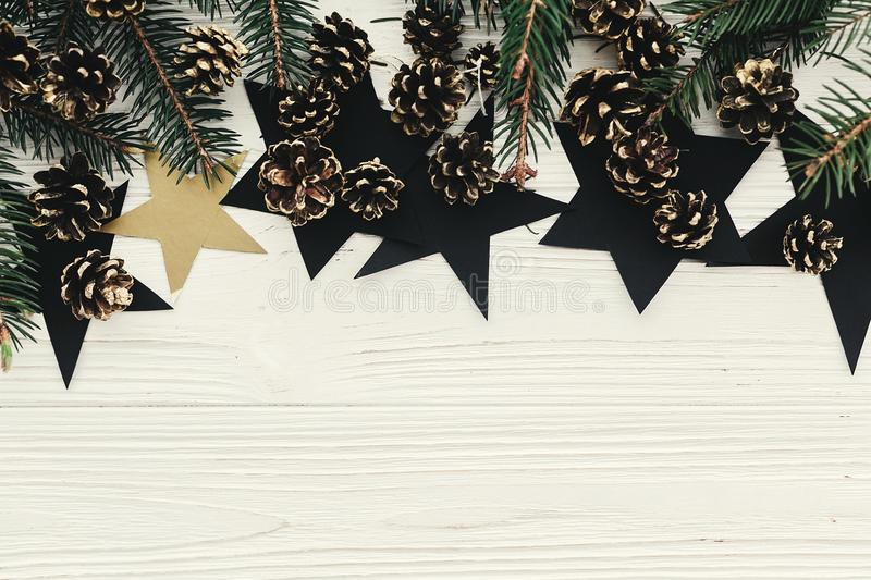 christmas flat lay. modern christmas layout with green fir branches, golden pine cones and stars, top view with space for text. h stock photography