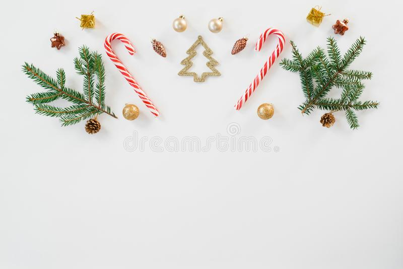Christmas and new year composition. Christmas gift, knitted blanket, cones, fir branches, candy cane on white wooden background. F royalty free stock images