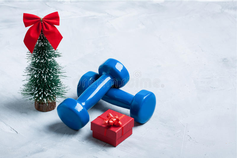 Christmas sport composition with dumbbells, red gift box, christ royalty free stock photo