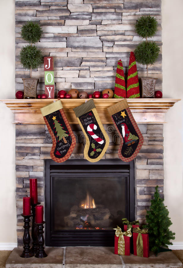 Christmas stockings hanging from fireplace. Christmas stocking hanging from a mantel or fireplace, decorated for Christmas with fire glowing stock photography