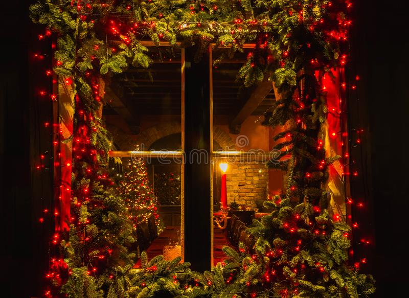 Christmas tree and fireplace seen through a wooden cabin window. Outdoor stock photography