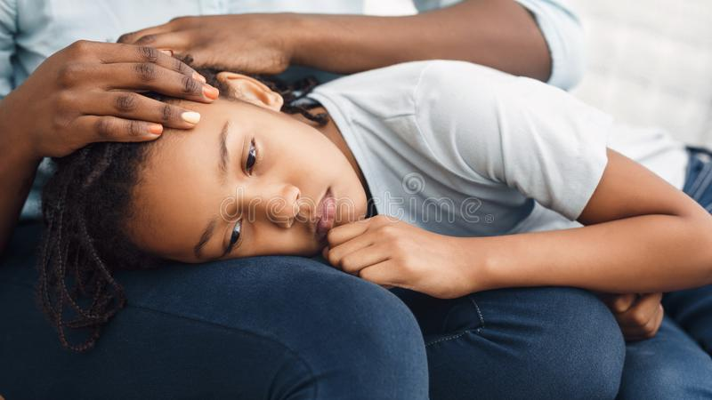 Close-up of black girl`s head laying on lap. Close-up Of Girl`s Head On Lap, African Mother Comforting Her Sad Child On Sofa At Home, Panorama stock images