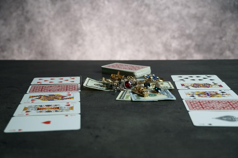 The combination of Flash Royal cards on a gray table with money and gold. Close-up. Poker game. Photo stock photos