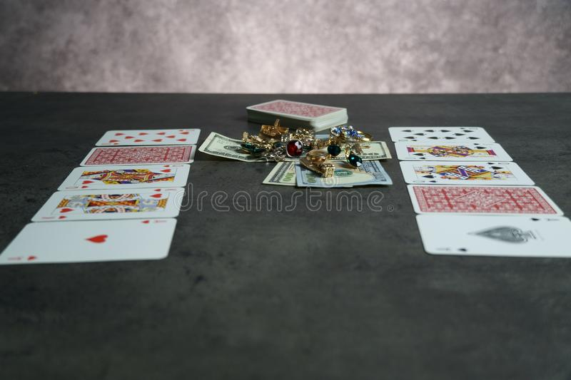 The combination of Flash Royal cards on a gray table with money and gold. Close-up. Poker game. Photo royalty free stock images