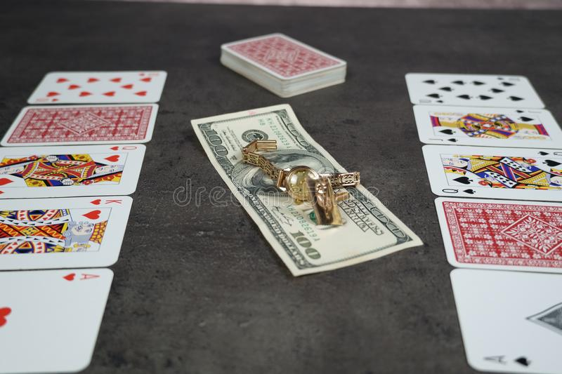 The combination of Flash Royal cards on a gray table with money and gold. Close-up. Poker game. Photo royalty free stock photo
