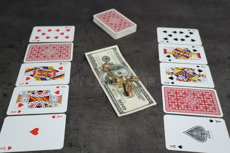 The combination of Flash Royal cards on a gray table with money and gold. Close-up. Poker game. Photo royalty free stock photos
