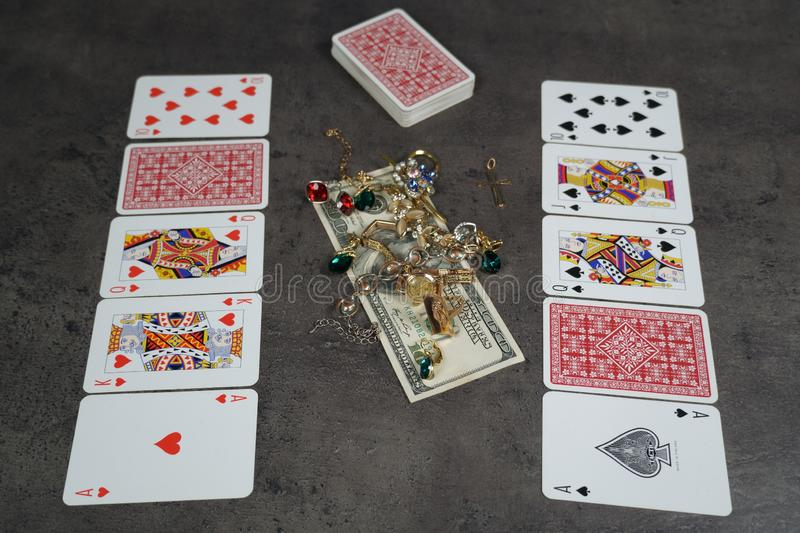 The combination of Flash Royal cards on a gray table with money and gold. Close-up. Poker game. Photo stock images