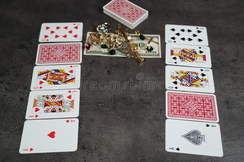 The combination of Flash Royal cards on a gray table with money and gold. Close-up. Poker game. Photo royalty free stock photography