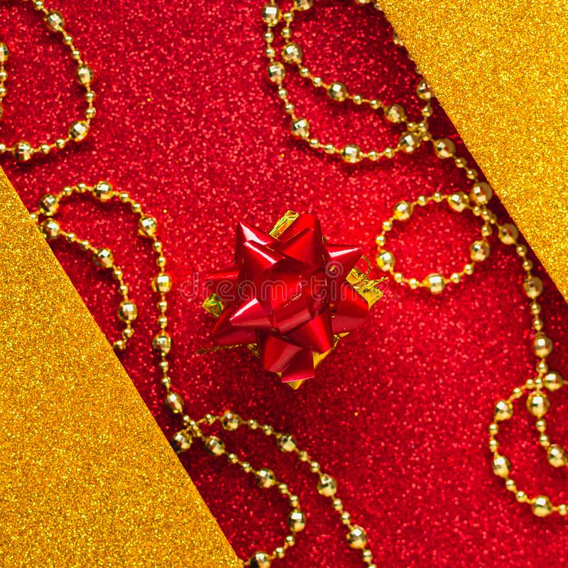 Combination of red and gold with a gift box, beautiful beads, a shiny holiday background. Christmas card, background for congratulations. A combination of red stock photo
