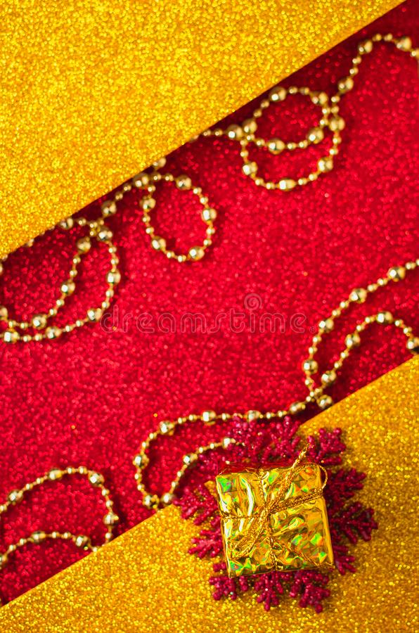 Combination of red and gold with a gift box, beautiful beads, a shiny holiday background. Christmas card, background for congratulations. A combination of red stock photography