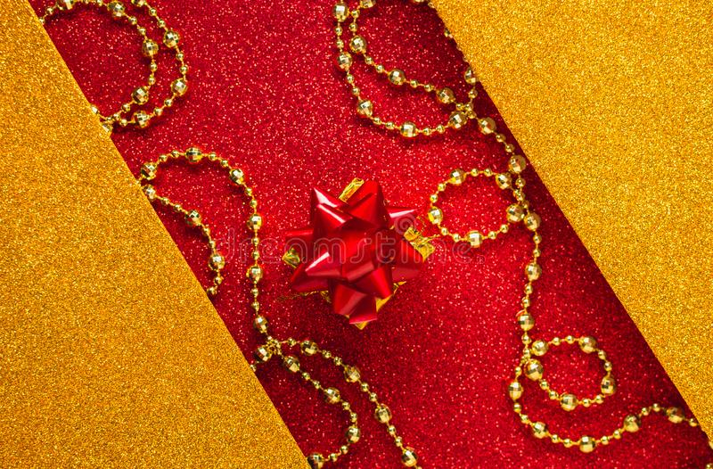 Combination of red and gold with a gift box, beautiful beads, a shiny holiday background. Christmas card, background for congratulations. A combination of red stock images