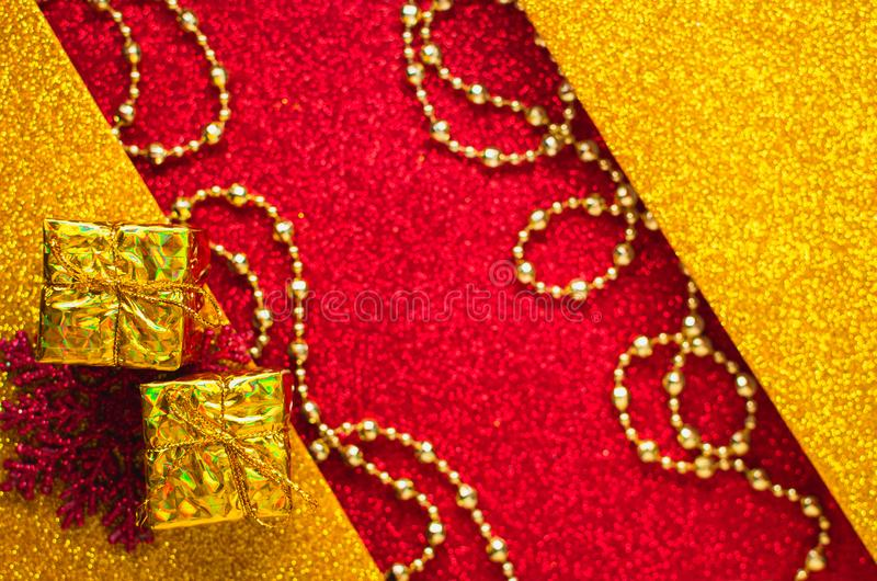 Combination of red and gold with a gift box, beautiful beads, a shiny holiday background. Christmas card, background for congratulations. A combination of red stock photos