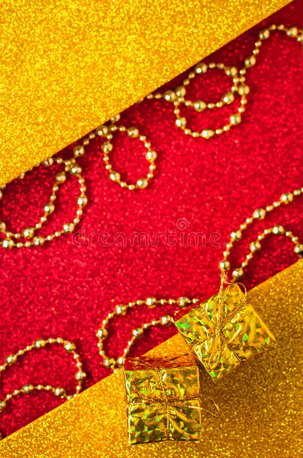 Combination of red and gold with a gift box, beautiful beads, a shiny holiday background. Christmas card, background for congratulations. A combination of red royalty free stock images