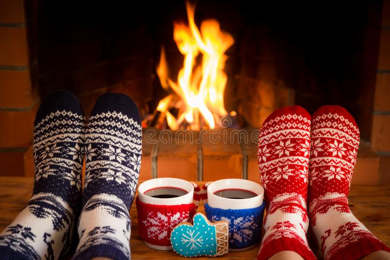 Couple in Christmas socks near fireplace. Friends having fun together. People relaxing at home. Winter holiday Xmas and New Year concept royalty free stock photo