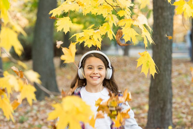 Crispy autumn air. Happy small child smile listening to music on autumn day. Little girl play on fresh air on autumn. Landscape. Smell the crisp air and feel stock image