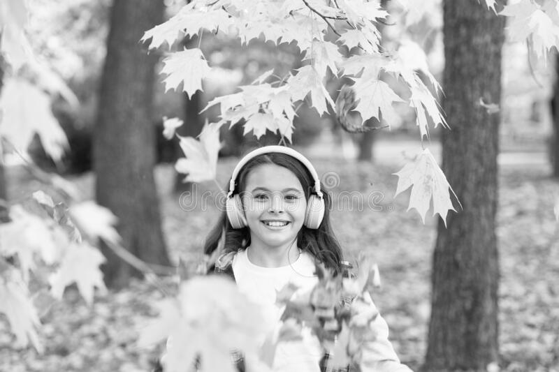 Crispy autumn air. Happy small child smile listening to music on autumn day. Little girl play on fresh air on autumn. Landscape. Smell the crisp air and feel royalty free stock photos