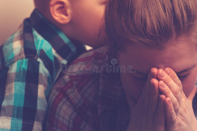 Crying unhappy mother with child at home. Crying unhappy women covering her face with hands while little child standing next to her. Tired and depressed mother stock photos
