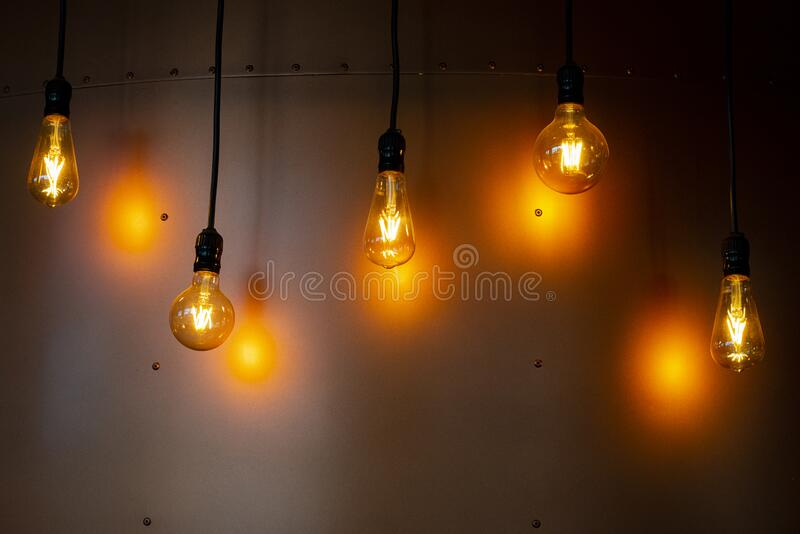 Decorative lamps with apparent filament. Metal background with exposed screws.  royalty free stock photography