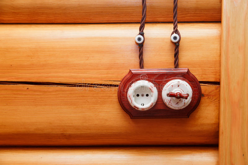 Electrical socket and switch in retro style on a wooden wall. Design of electricians in the house. royalty free stock image