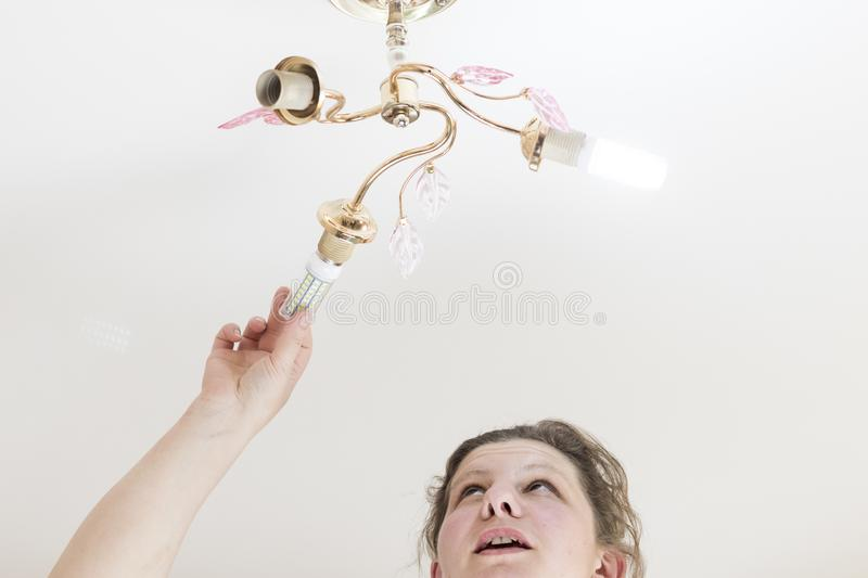 Female hand inserts a light bulb into the threaded socket. she is shining. Installation of household LED lamps of corn type, in. The lamp holder, there is a royalty free stock image