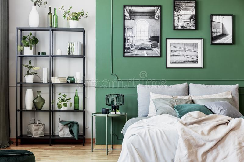Gallery of black and white poster on green wall behind king size bed with pillows and blanket stock photo