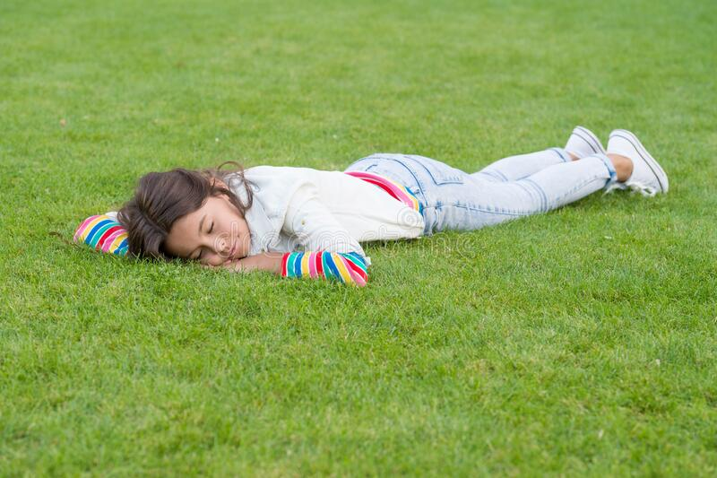 Healthy sleep on fresh air. happy child lying on grass. dream. small girl relax on green grass. spring is here. human. And nature concept. kid enjoy summer stock photo