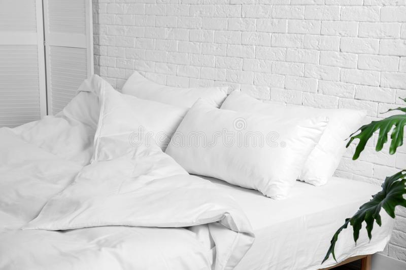 Large comfortable bed with pillows and blanket near white brick wall indoors stock photography