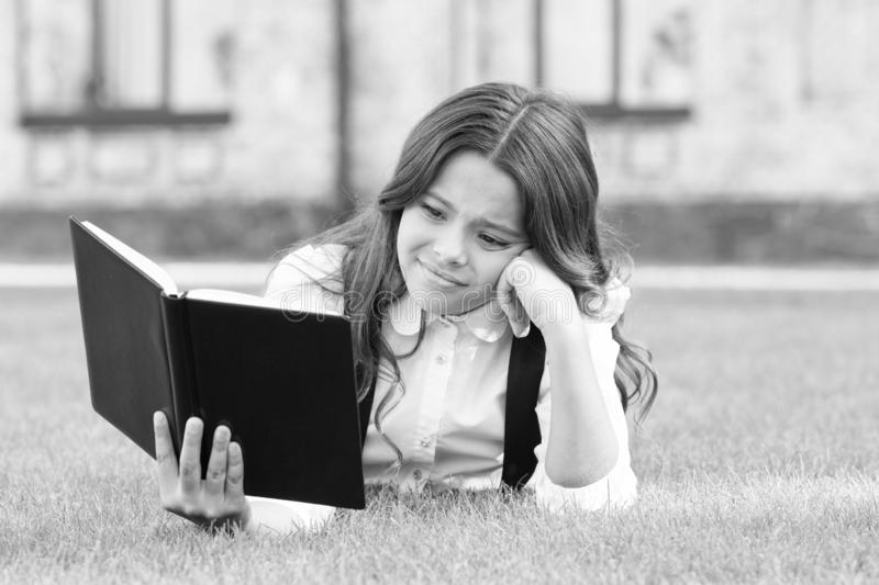 Literature for kids. Lesson on fresh air. Cute small child reading book outdoors. Schoolgirl school uniform laying on. Lawn with favorite book. Studying concept royalty free stock photography