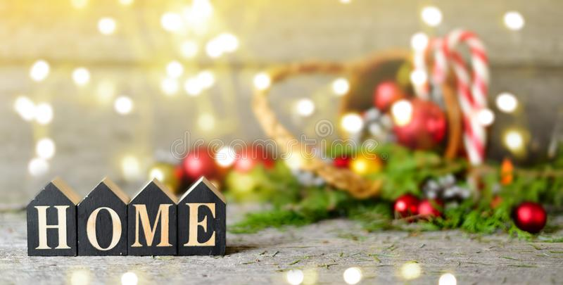 Long banner Christmas composition with and Shining lights. Red balls, Pine cones, lollipop, toy houses text Home on Wooden Table royalty free stock image