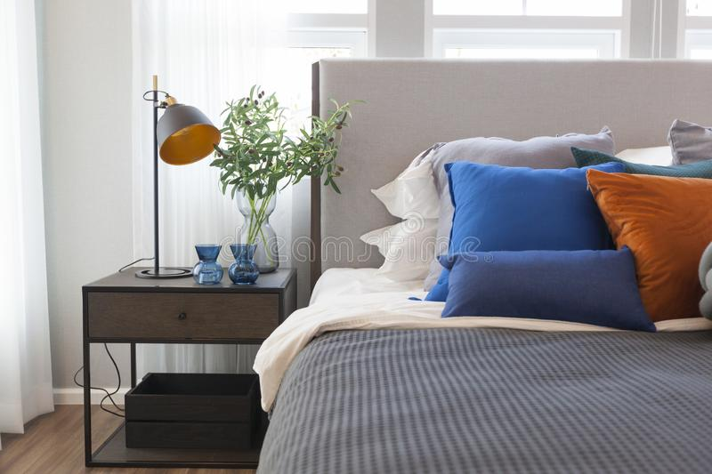 Modern bedroom in minimalist white and blue interior tone with with side table and table lamp. stock images