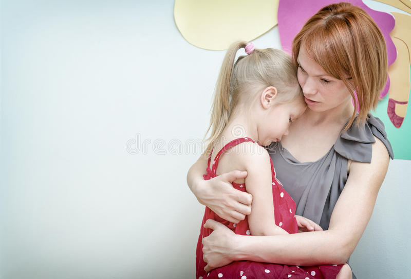 Mother hugging her child. Mother hugging her sad child stock photos