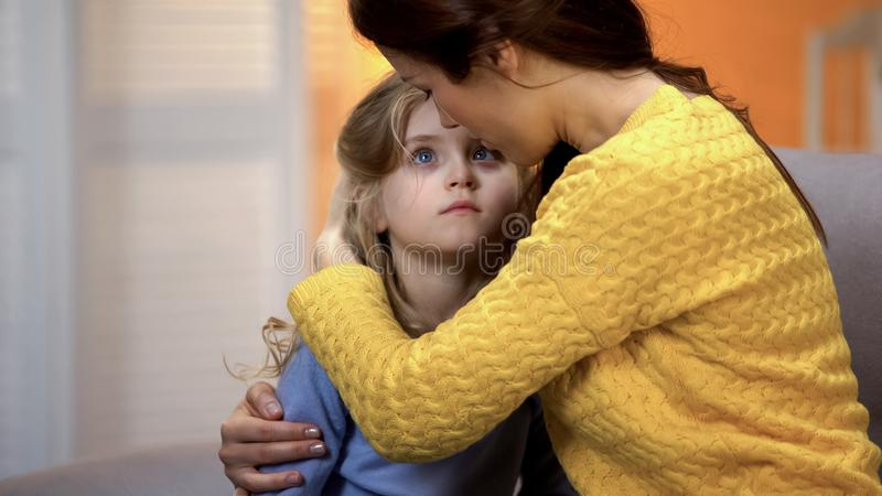 Mother hugging sad little adorable girl home after work, family love and care. Stock photo stock photography