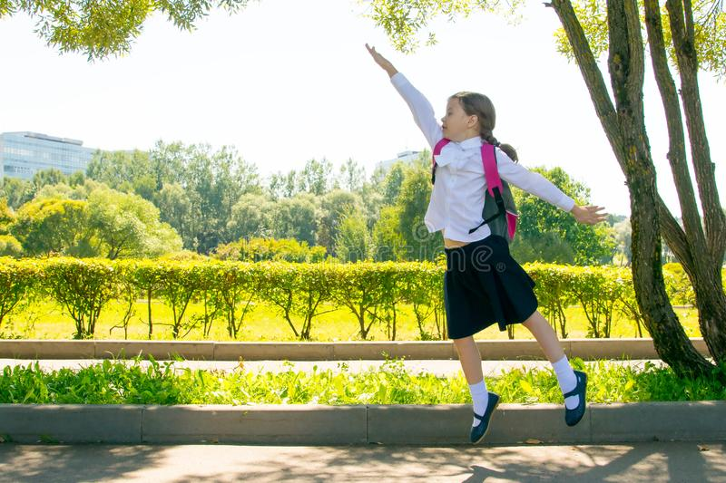 In the park, in the fresh air, a schoolgirl is having fun and jumping up, raising her hand stock photo
