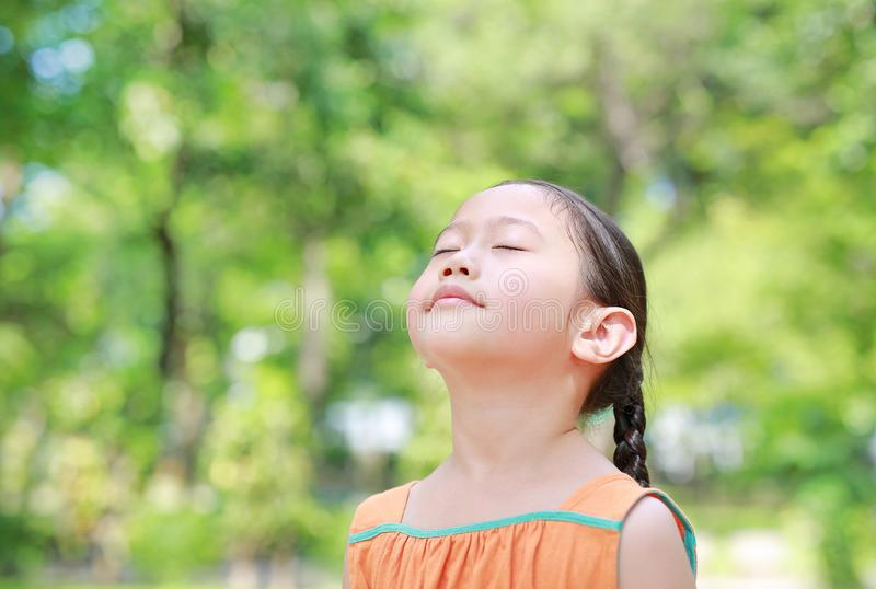 Portrait of happy Asian child close their eyes in garden with Breathe fresh air from nature. Close up kid girl relax in green park. For good health stock images