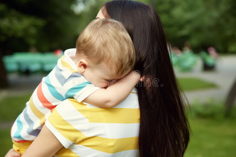 Portrait of mother and son. Outdoor portrait of mother and son. child and mom walk in the summer park. sad crying baby royalty free stock image