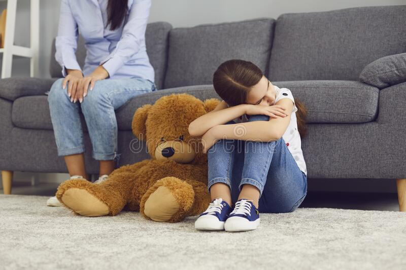 Sad offended child sitting on the floor does not talk with mother in the room. The problem is the relationship between mother and child in the family. Conflict royalty free stock photos