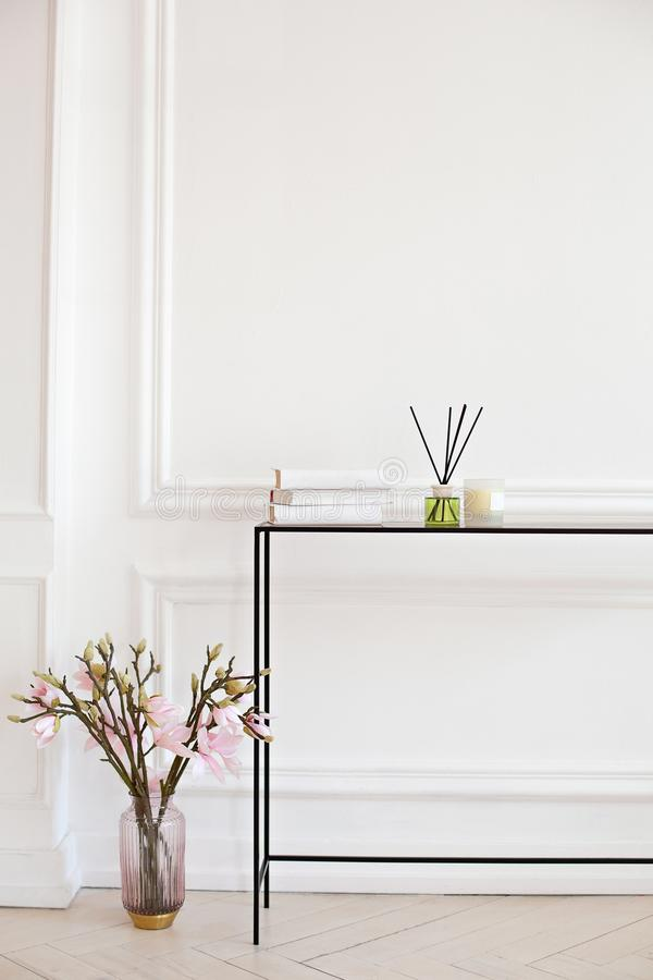 Reed diffuser on the table in the living room. Manual reed freshener with a candle on the dresser in the bedroom. Scandinavian hom stock photo