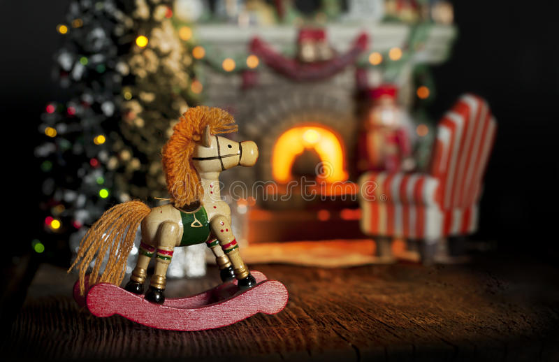 Rocking Horse Christmas Fireplace. A vintage style rocking horse with decorated Christmas tree, comfortable chair, and burning fireplace blurred in background royalty free stock photos