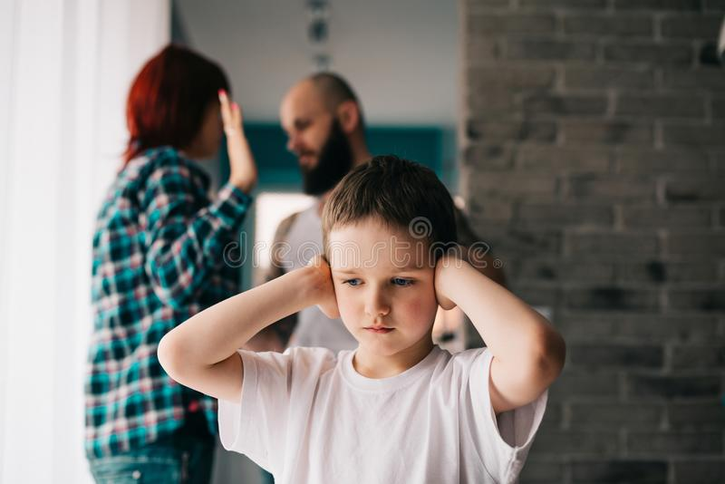 Sad child covering his ears with hands during parents quarrel. Man about to beat his wife stock photos