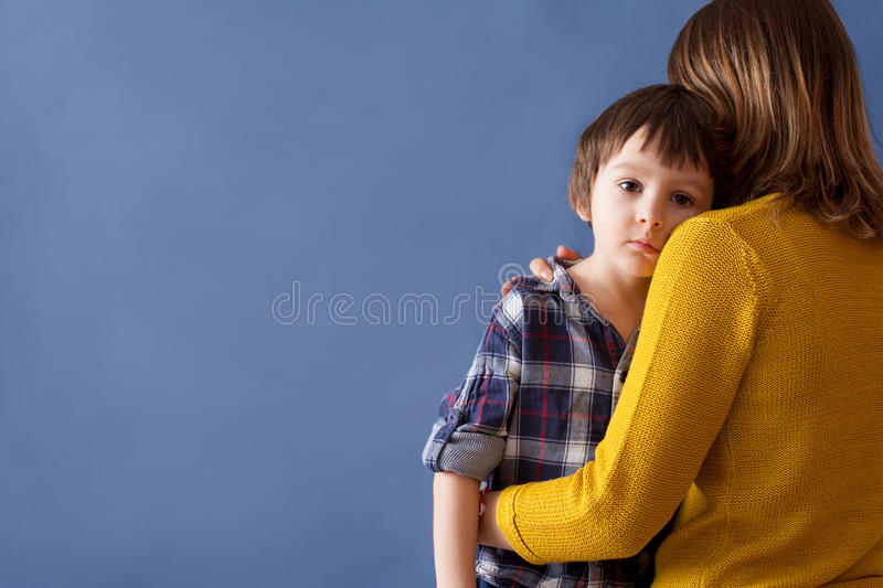 Sad little child, boy, hugging his mother at home. Image, copy space. Family concept stock image